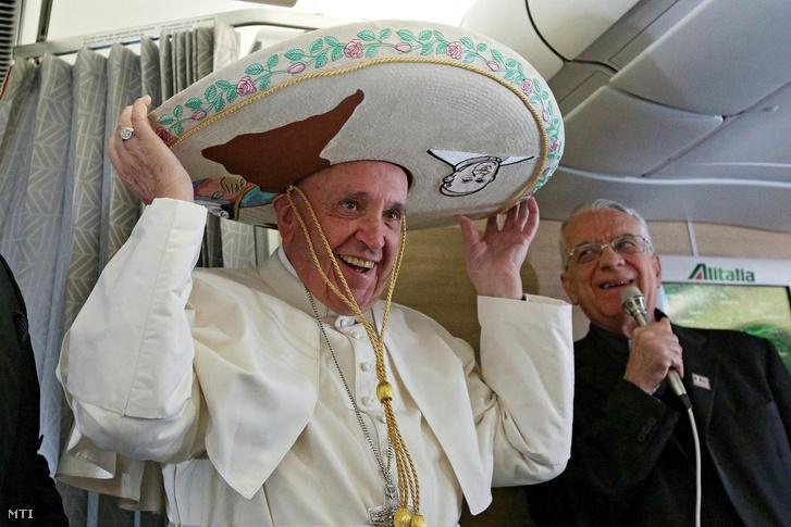 Ferenc pápa egy újságírótól ajándékba kapott mexikói sombrerót visel a Rómából Havannába tartó repülőgép fedélzetén.