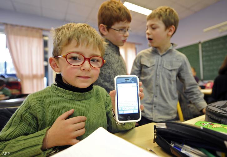 Gyerekek használják iskolájukban az okostelefonjaikat.