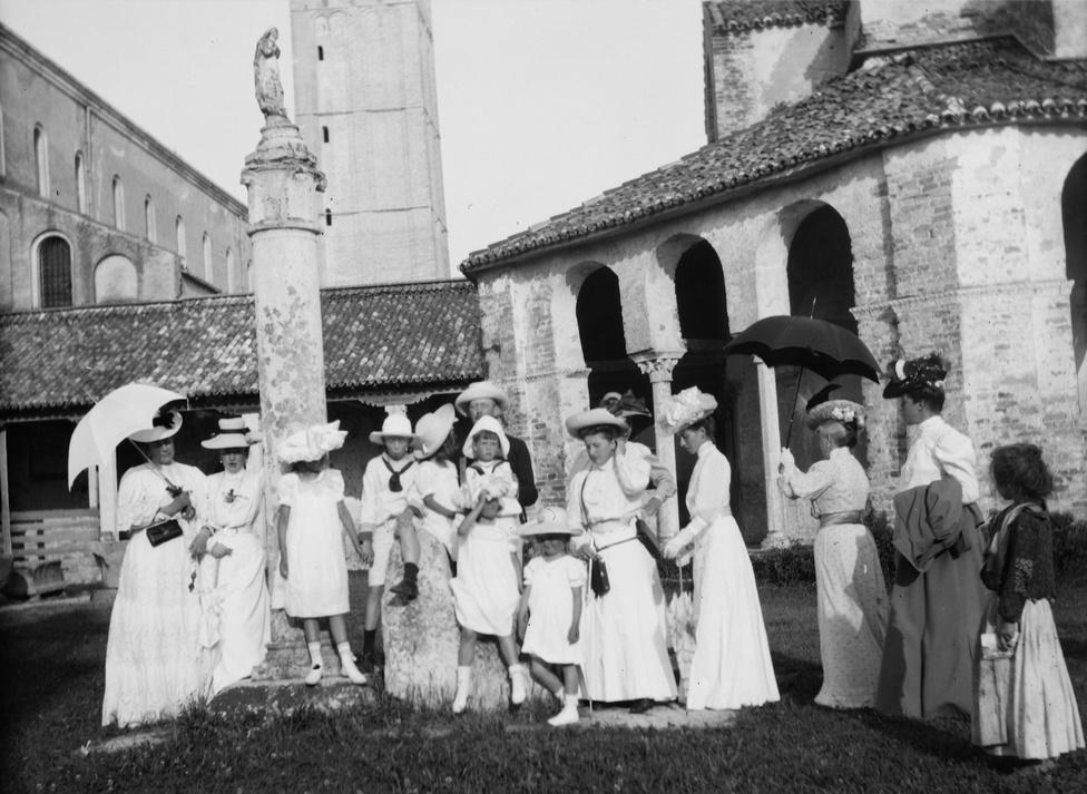 """A Velence melletti Torcello kolostora, a ma gyakorlatilag elhagyott műemlékszigetet akkor még lakták. Aznapra láthatólag mindenki fehérbe öltözött, kivéve a kép szélén látható helyi kislányt, aki talán kéreget, vagy inkább képeslapokat próbál eladni az utazóknak. Jelenléte azért is lehet feltűnő, mert egyébként erről a fotósorozatról szembeszökően hiányoznak a kívülállók. Nem véletlenül: az arisztokrata elit olyan életet igyekezett élni, amelyben csak nagyon szűk keretek között van lehetősége """"alsóbbrendű halandóknak"""" kapcsolatba kerülni a család tagjaival - a nőket végképp óvták attól, hogy ilyesminek tegyék ki őket."""