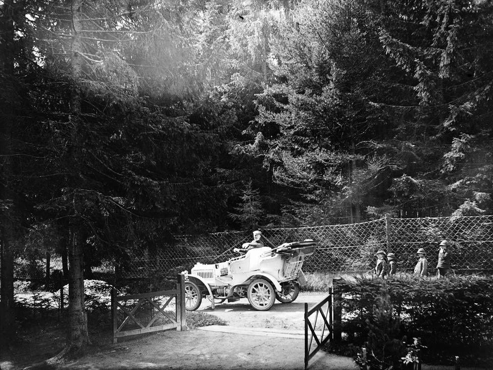 A fenyvesekből ítélve talán ez a kép is a Tátrában készült - egyébként az egyik első magyar autóverseny is ide vezetett Budapestről; az út akkor szinte annyi megpróbáltatással járhatott, mint most egy Párizs-Dakar rali. Az itt látható autó egy Mercedes, de még nem Benz, a típus a gyáregyesülés előtt készült. A gépkocsi tulajdonosa a Magyar Automobil Club 1906-os évkönyve szerint gróf Zichy Béla Jenő.
