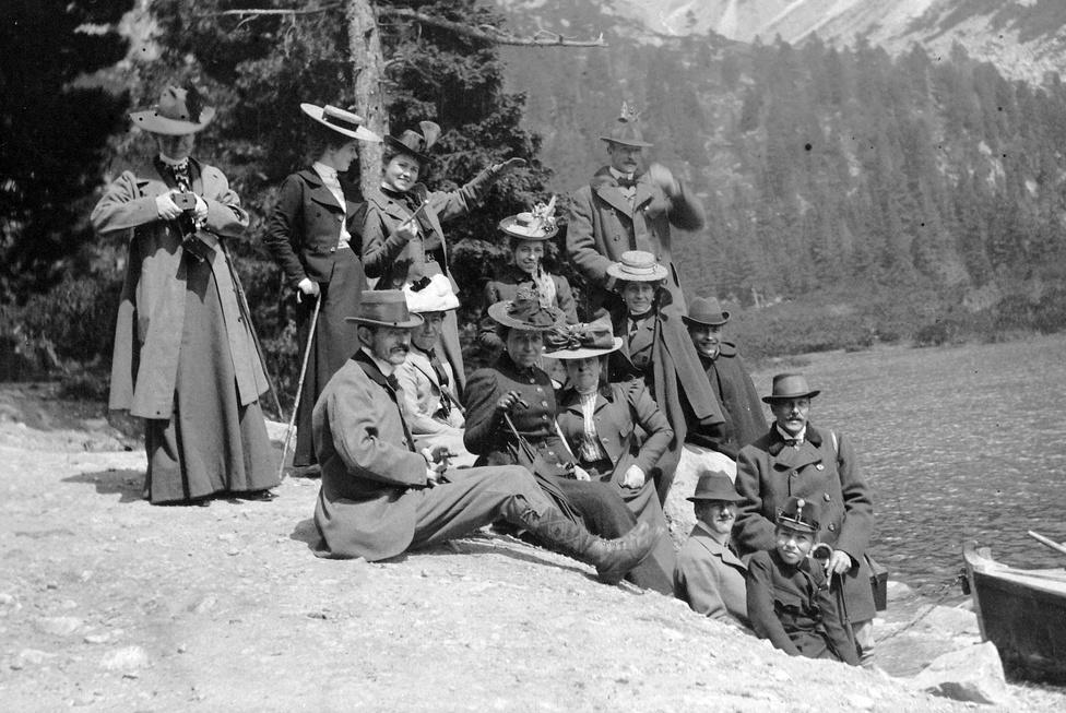 Tátrai nyaralás, talán a Csorba-tónál; Tátralomnic volt egyébként az arisztokrata társaság legfőbb hegyvidéki pihenőhelye. Ezen a képen is feltűnő lehet a kirándulók minőségi anyagokkal kivitelezett eleganciája - más rétegek nem csak  túrázni jártak ennél egyszerűbb ruhákban. A lovaglópálcás hölgy mintha valakinek a méretével viccelődne, de talán érdekesebb két alak a szélekről. Balra valaki szembefényképez velünk, méghozzá ez a valaki egy hölgy - ami az egyébként szigorú etikett szerint élő elit társaság viszonylag emancipált szabadidős formáiról is tanúskodhat. A csónak mellett ülő fiú mintha kicsit kilógna a többiek közül - ha valaki meg tudná fejteni, köszönjük ha jelzi: egy fiatal csónakosról, avagy a társasághoz tartozó kadétról van-e szó.