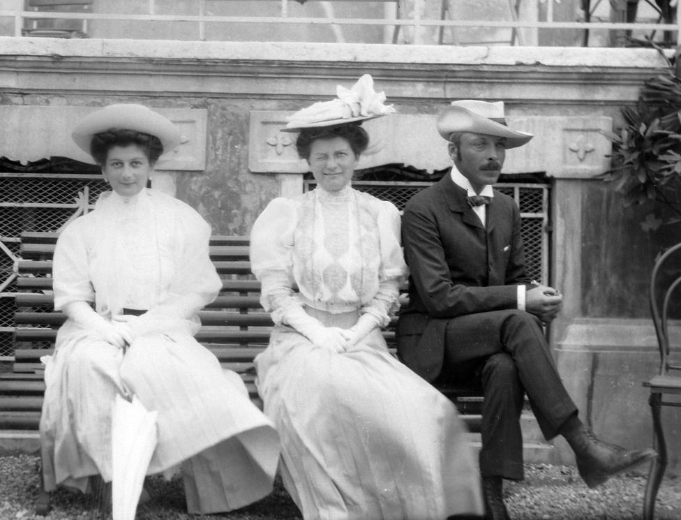 A velencei Grand Hotel des Bain előtt egy itáliai utazáson. A Zichy család utazási szokásait tekintve az európai arisztokrácia jellegzetes tagjai közé tartozott, a képeken is több hosszabb útról maradtak fent képek. Elegendő szabadidőnek és a szükséges pénznek sem voltak híján, de az akár évi több hónapos utakat a nemzetközi arisztokráciával való kapcsolattartás is indokolhatta. A bajszos úr a képen a fotósorozat egyik főszereplője: feltehetően ő Zichy János legitimista politikus, a tízes években kétszeres kultuszminiszter.