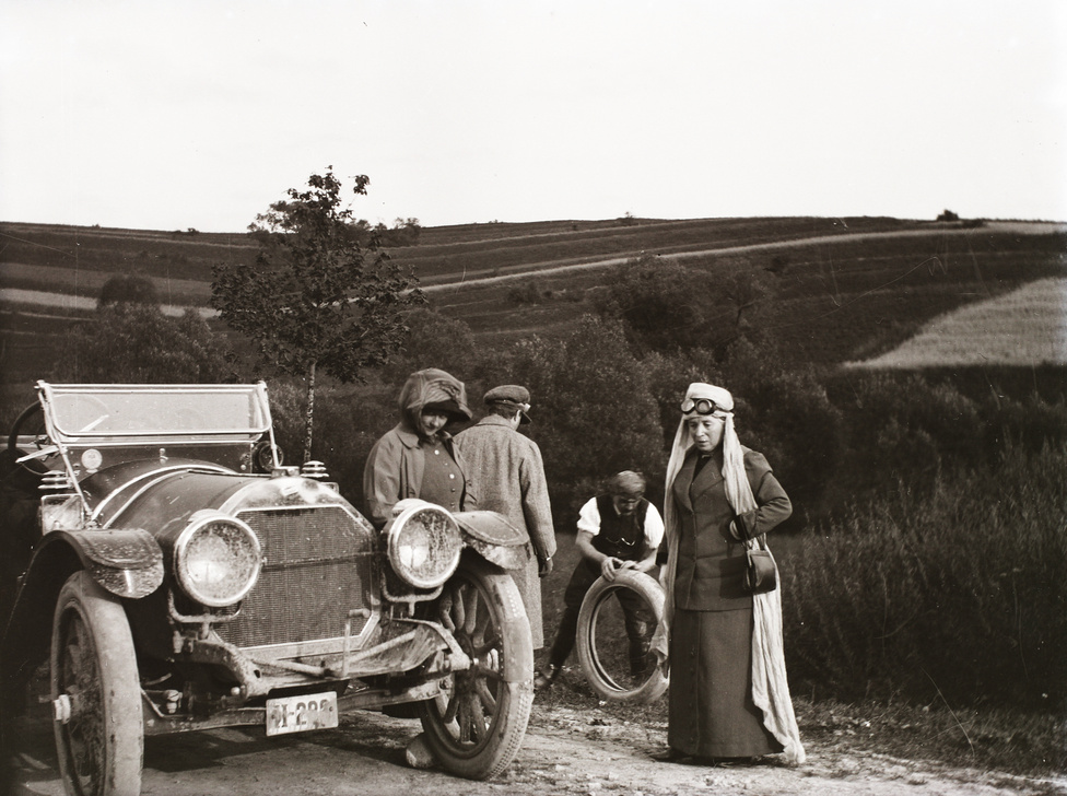 Útszéli defekt, a gumitömlővel a sofőr, az autón 1922 előtti rendszámozás. A római II-es a fővárosi autóké volt, a gépkocsik ritkaságát is jelzi, hogy ezután elegendő volt három számjegynek állnia. Az első automobil kluboknak sok arisztokrata tagja volt, ahogy az autóversenyzés is költséges úri passsziónak számított eleinte. A mágnások más tekintetben is az új luxusfogyasztási formák korai elfogadói közé tartoztak, a repülés és több frissen divatossá vált sportág is jól működött a hivalkodó életstílus kellékeként.