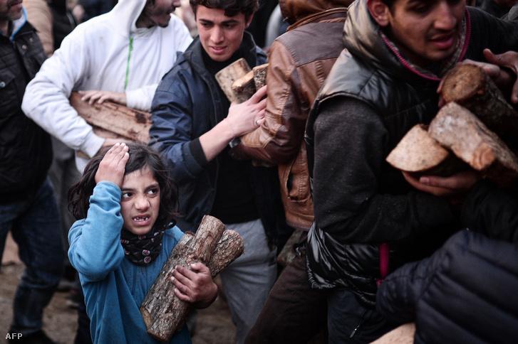 Menekültek tűzifával az Idomeni közelében létesített befogadótáborban, a macedón-görög határnál 2016. március 6-án