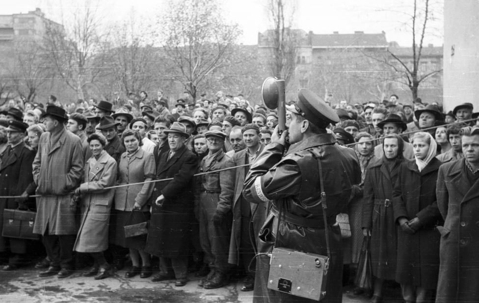 Nézelődők a Köztársaság téren, a Pártházhoz tartozó feltételezett kazamaták keresésekor. A tömeget hangszórós rendőr                          próbálja visszatartani a kiásott gödörtől.