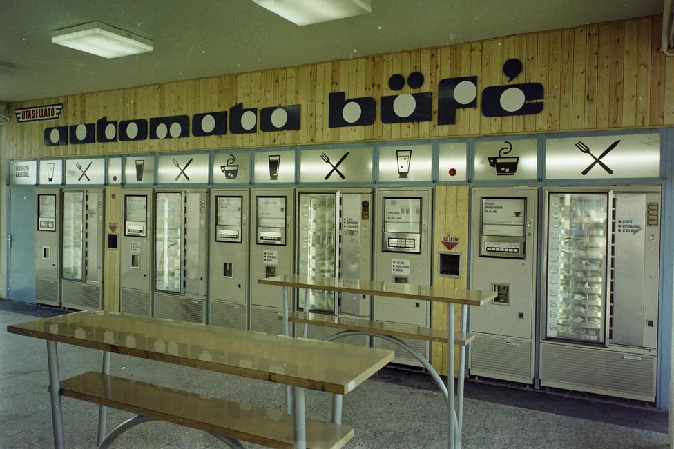 Vidéki gyerekként a nyolcvanas években sokszor jártam a fővárosban, vonattal érkeztünk a Keletibe, innen jellemzően metróval mentünk tovább. Budapestről az egyik visszatérő emlékem, hogy borzasztóan menőnek és nagyvárosinak tartottam - és talán nagyviláginak is tartottam volna, ha ismerem kisgyerekként ez a szót -, hogy vannak ételautomaták. A Batthyány téren volt egy kedvenc forrócsokis automatám - nyilván annak élményei segítettek elhomályosítani a tényt, hogy egyébként ezekből az automatákból a sima utasellátósnál is szárazabb, szöttyedt zsömléket lehetett kapni, szomorkás párizsiszeletekkel, látszatvajjal, fonnyadt zöldséggel vagy száraz sajtdarabbal. De akkor is: az ételautomata nekem a világvárosiasság szimbóluma volt, akárcsak a metró vagy az önkiszolgálók (erre még visszatérek).                         Az Utasellátó Vállalatot 68 évvel ezelőtt alapították: a Minisztertanács határozata nyomán 1948 novemberében kezdte meg a működését, és a kezdetektől a MÁV égisze alá tartozott. De természetesen a vasúti utasellátás sokkal korábbra nyúlik vissza: 1889-től közlekedtek a magyar vasúton rendszeresen háló- és étkezőkocsik.