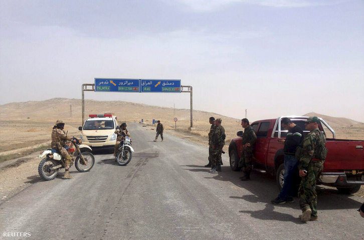 Szíriai kormányerők egy ellenőrzőpontnál, a háttérben a táblák a Palmüra felé vezető utat jelölik a híres romok közelében.