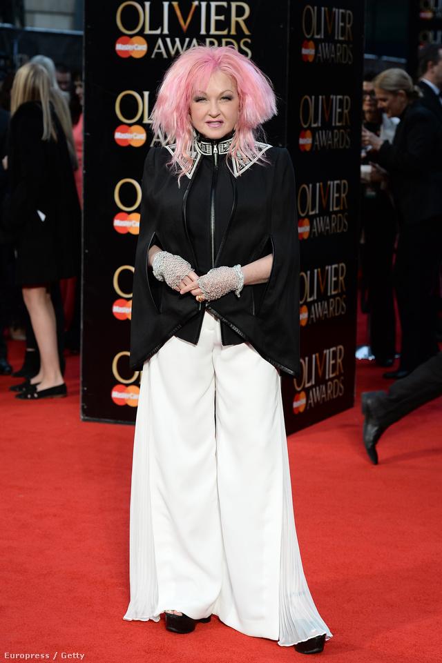Meglepő, de Cyndi Lauper már 62 éves. Ennek ellenére egy igencsak fiatalos külsővel, pink hajjal, fehér bőgatyában és ezüst gallérral díszített fekete pelerin kabátban jelent meg az eseményen.