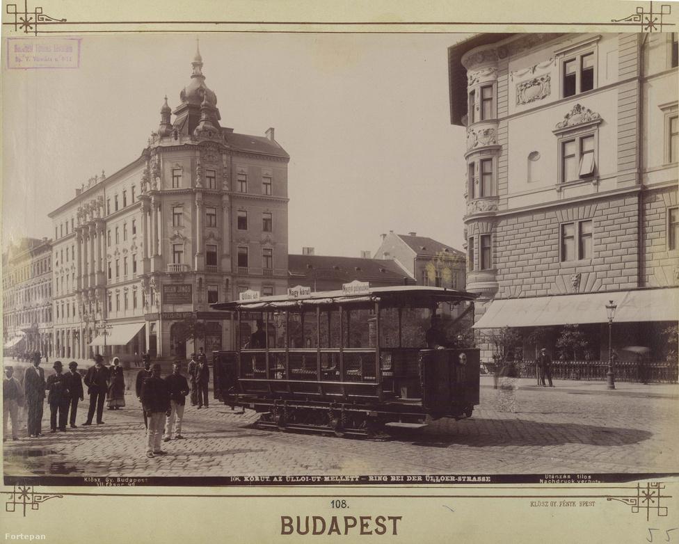 """Az 1890-es évek elején készült fotón a Nagykörút máig nélkülözhetetlen kelléke, a villamos. Ez még nem a négyeshatos, az útvonala is rövidebb: az Üllői út és a Nyugati pályaudvar között közlekedett. Nem az 1887-ben megjelent villanyos volt az első tömegközlekedési eszköz, a ló(fejű)vasút megelőzte. Mikszáth például soha nem tudta megszokni: """"Egy ormótlan nagy szekér, amely mindenkit fölvesz egy hatosért, mely minden utca szögletén megáll, mikor az ember siet, és nem ott áll meg, ahol az ember akarja, hanem ahova a direkció a 'Haltepunkt'-póznát beszúrta. Ez a rettenetes kimértség megöli a nervózus embert s meggyűlölteti vele a XIX. századot.""""Háttérben balra a Ferenc körút díszes bérháza, jobbra a József körút saroképülete, alatta a Valéria kávéházzal."""