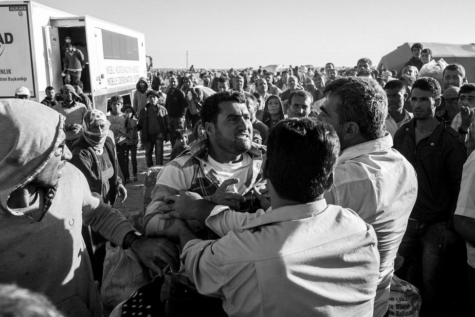 Férfiak vitatkoznak a határon. A létszámkorlátozások miatt mindennaposak voltak a kisebb verekedések. A helyzet idén március óta még rosszabb, mert sokakat visszatoloncolnak a törökök.