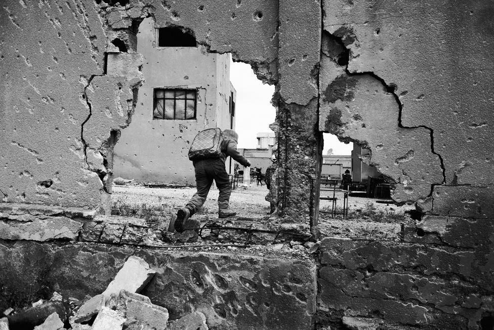 Iskolába tartó gyerek Kobanî romjai között. Az észak-szíriai kurd város a 2011 óta tartó polgárháború egyik legismertebb helyszíne. Az Iszlám Állam 2014-ben vonta ostroma alá, a felszabadítása alatt az Egyesült Államok vezette koalíció itt bombázott a leghevesebben az egész konfliktus alatt. Kobanî olyan szimbóluma az emberi kegyetlenségnek, mint Szarajevó volt a délszláv-háború alatt. Civilek ezrei haltak meg az etnikai alapú mészárlásokban, a becslések szerint 200 ezer ember menekült át a közeli Törökországba, hogy onnan várja meg a harcok végét.