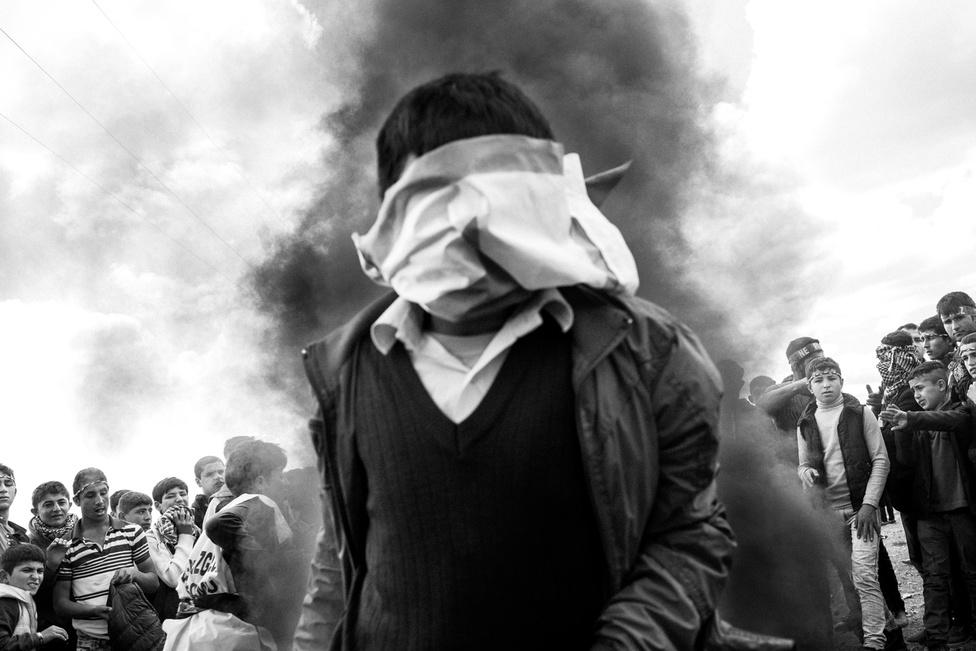Ez nem egy gyerekkatona. A 12-13 éves fiú a Newroz alatt állított máglyát ugorja éppen át. A kurdok nemzeti ünnepét március 21-én tartják. Ilyenkor arra emlékeznek, hogy a médek legyőztek a zsarnok asszírokat, ekkortól számítjuk a népük megszületését. A kép a törökországi Surucban készült, ahogy Temir legtöbb fotója. A város menekülttáborában 25-40 ezer kurd várakozik arra, hogy visszatérhessen Szíriába. Többségük – közel 70 százalékuk – nő és gyerek, a férfiak vagy otthon háborúznak vagy előre indultak Európába, hogy a családjuk ne a semmibe érkezzen.