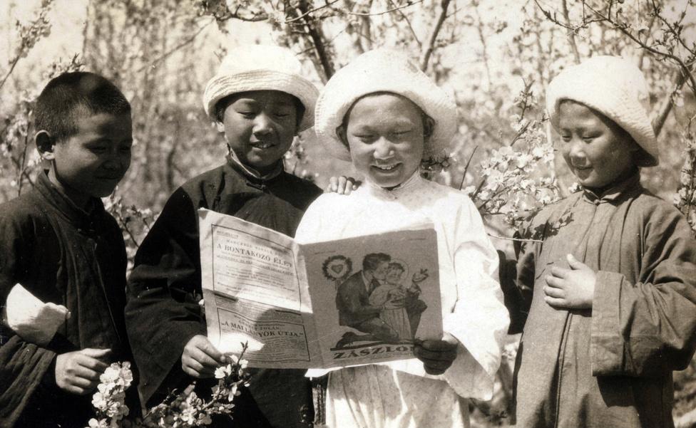 Magyar nyelvű katolikus diákújságot nézegetnek a jezsuitáknál tanuló kínai gyerekek. Nem sokat érthettek belőle: bár az iskolában tanultak latin írást, magyarul nem, ha már valami, a francia volt a közvetítő nyelv. A kép inkább az otthoni adományozóknak szólt, félig-meddig poén lehetett, azt is szemléltetve persze, hogy jó helyre kerülnek a misszióra szánt pénzek.
