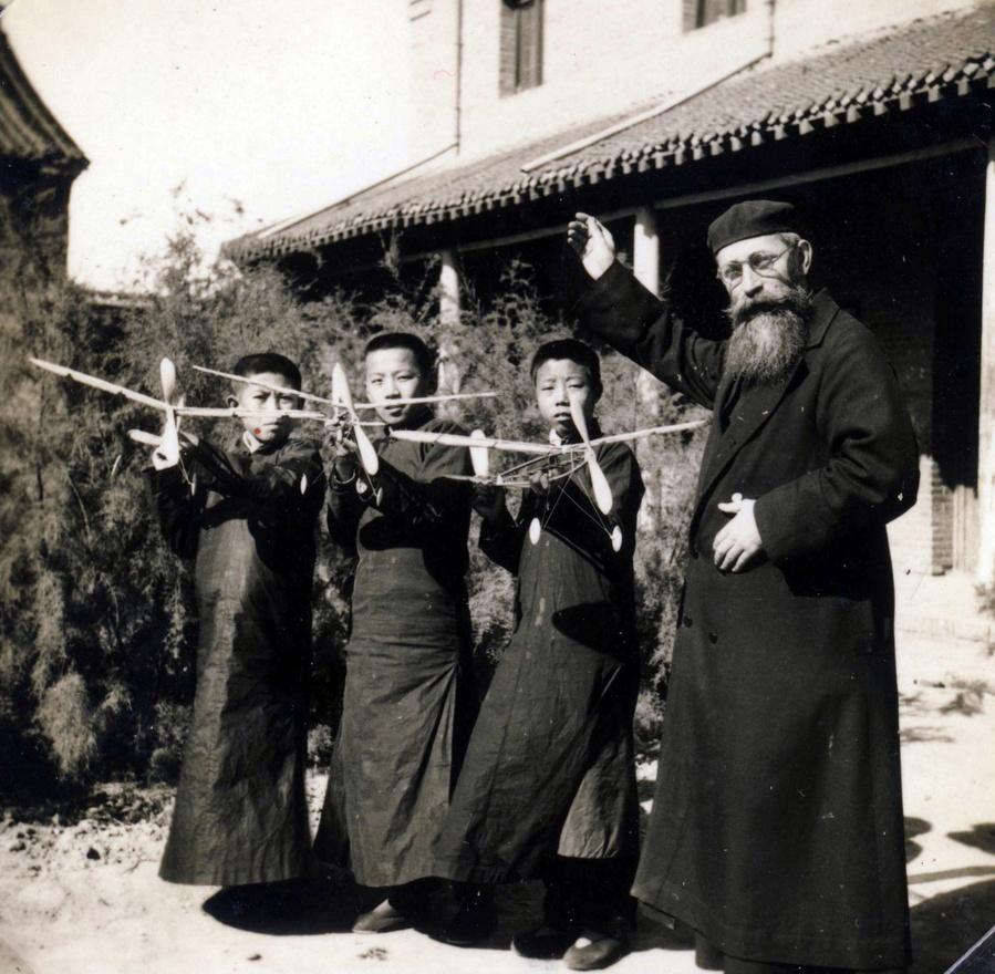 Litványi kínai diákokkal és repülőgépmodellekkel. A jezsuita iskolákban magas színvonalon oktatták a természettudományokat és a modern technikai ismereteket. Komoly hangsúlyt fektettek az idegen nyelvek oktatására is, de ekkor jelentek meg elsőként Kínában a zenei ismeretek és a testnevelés is.
