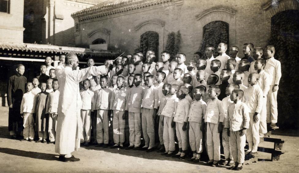 A Támingban működő jezsuita misszió egy szegény, messzebbi külvilággal testközelből először rajtuk keresztül találkozó vidéken dolgozott. Az 1920-as évekig gyakorlatilag a nyugati misszionáriusok iskoláit kivéve nem volt modern oktatási rendszer Kínában, a vidéki lakosság zöme írástudatlan volt. A képen Litványi György (1901, Komárom – 1983, Tokió), az iskola prefektusa a kínai diákok kórusával.