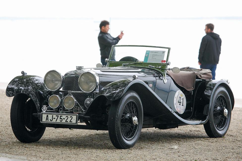 Balatonfüred legszebb nyitott autója: SS 100 Jaguar (1936). A cég kezdetben Swallow Sidecars néven futott, de a második világháború idején az SS név nem volt valami népszerű Nagy-Britanniában, ezért 1943-tól hivatalosan felvették a Jaguar nevet – a nagymacska addig csak hűtődíszként ugrált a kocsi orrán. Elég gyorsan, mert ez volt az első típusuk, amely megfutotta a 100 mérföld per órát (161 km/h).