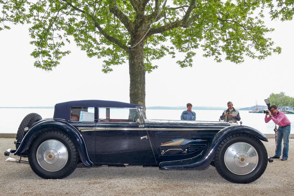 Talán az egész kiállítás legkülönösebb darabja a Bucciali-Cord L29 (1931/2012). A grandiózus kocsi mellett eltörpül a néző, az alacsonyabbak vállmagasságban szemlélhetik a 38 x 7 méretjelzésű pótkereket. Az a négy kerék, amelyeken gördül a gép, derékig ér. A történet nagyon bonyolult, a lényeg az, hogy a Bucciali testvérek egyre nagyobb és különösebb kocsikat építettek, korukat megelőző műszaki megoldásokkal, a cél az volt, hogy minél több szabadalmat adhassanak el. A Cord az elsőkerék-hajtás elterjesztésével tűnt ki, a karosszériát a Saoutchik készítette, Bucciali-tervek alapján. Ezt az autót fotók nyomán építették, a család leszármazottai is nevüket adták a projekthez, igaz, nem kis pénzért.