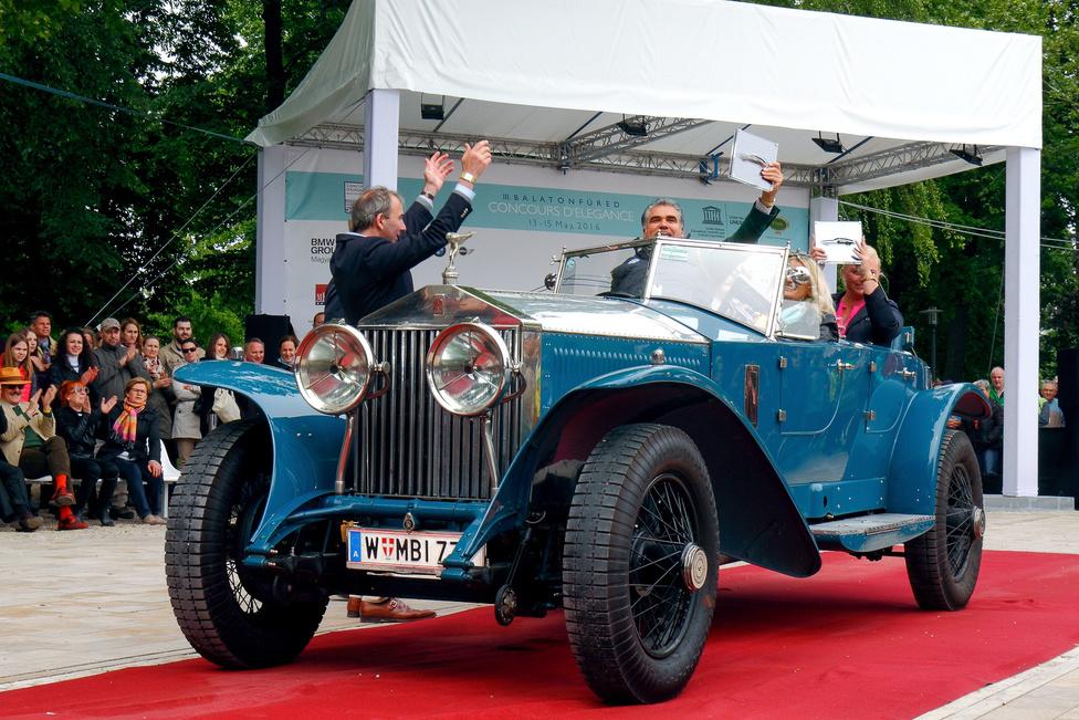 """Az osztrák illetőségű Rolls-Royce Phantom I (1928) Boattail, azaz """"csónakfarú"""" felépítményt visel, amelyet a Wimbledonban működő Jarvis cég készített. A hathengeres, 7668 köbcentis motorú kocsi 4350 mérföldes tesztelését maga Henry Royce végezte, mielőtt leszállították volna a kasmíri maharadzsának. Az autó négy díjat nyert: ez lett a legszebb nyitott kocsi a Vintage kategóriában, a BMW és a FIVA díja mellé bezsebelte a hölgylátogatók különdíját is."""