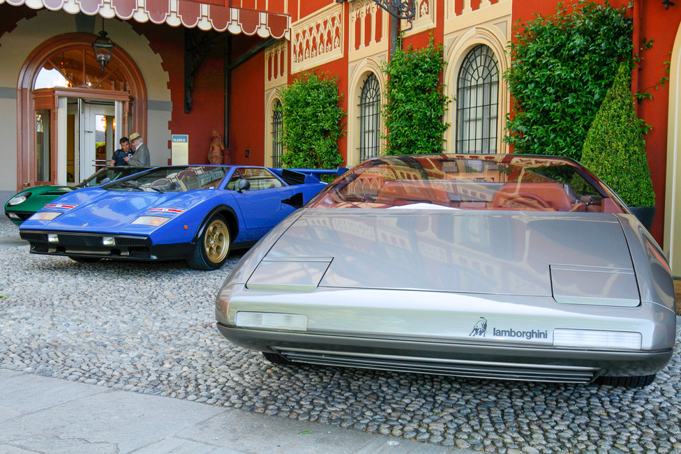 """Olaszországban vagyunk, tehát nem hiányozhatnak a Lamborghinik! Hátul egy Miura, mellette egy igen ritka Countach LP 400 Walter Wolf és az egyedi Athon. Az első kettőt Marcello Gandini tervezte, mint a Bertone stúdió fődizájnere, az Athont pedig utódja, Marc Deschamps. Az excentrikus olajmágnás, Forma-1 csapattulajdonos Wolf igényei szerint épült Countach megnyerte kategóriáját, melyet tán """"Mértéktelenségtől vezérelve""""-nek fordíthatnánk, az Athon pedig a """"Legizgalmasabb dizájn"""" díját vihette haza Svájcba"""