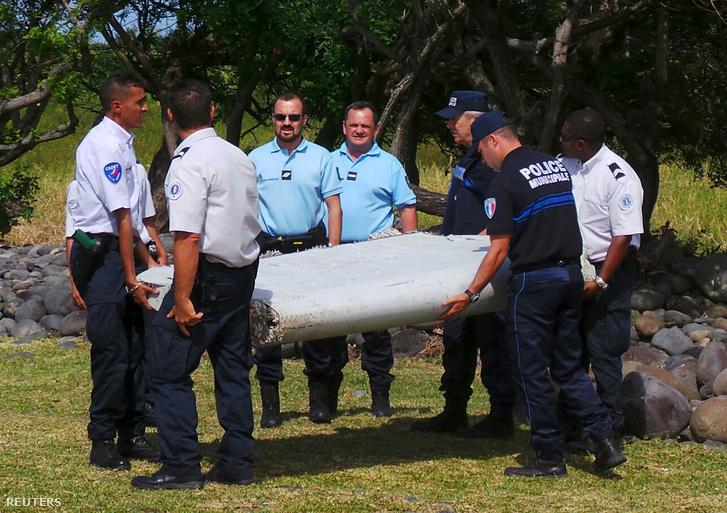 Francia rendőrök a maláj repülőgép szárnydarabjával, amit az Indiai-óceánban, Madagszkár és Reunion szigetek közelében találtak