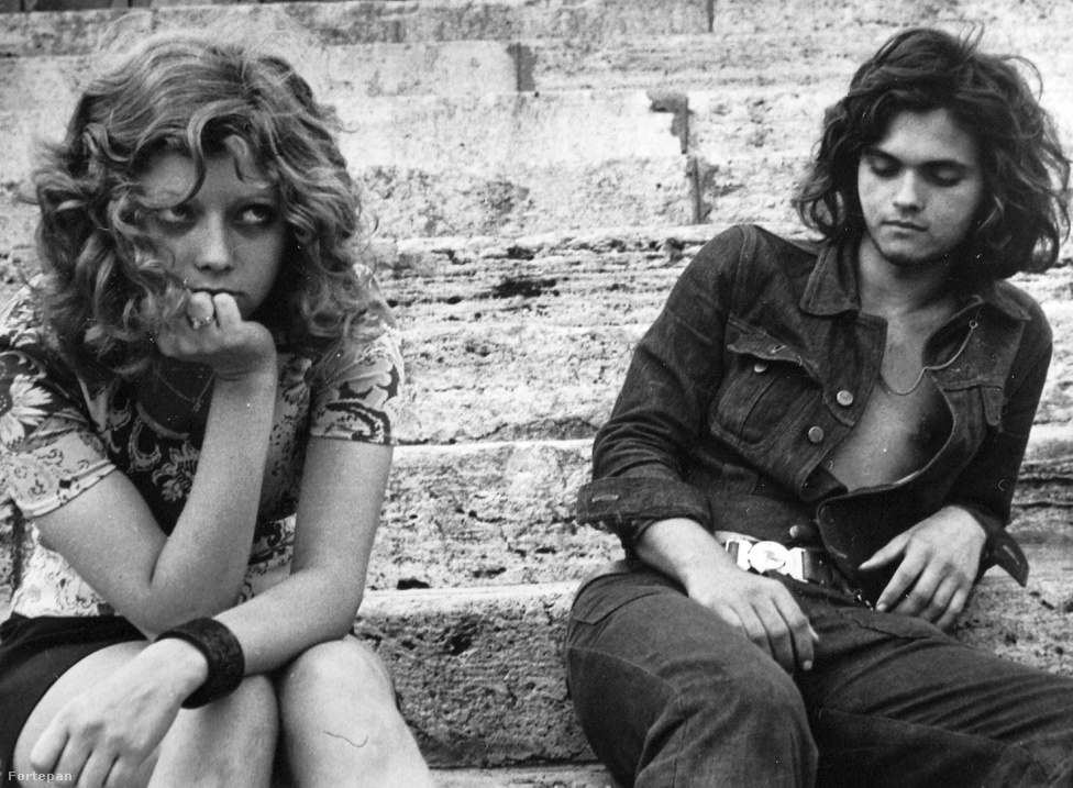 """A nyolcvanas években a domesztikált lázadás egyik sajátos kifejeződése volt az úttörőövvel hordott trapézfarmer is, ami tökéletes szimbóluma a Kádár-rendszer nyomasztó mindenhatóságának. """"Amíg 1971-ben farmerban és hosszú hajjal tilos volt belépni a Budai Ifjúsági Park területére, addig öt-tíz évvel később már az lett volna a mulatságos, ha valaki öltönyben és nyakkendőben akart volna részt venni egy rock koncerten. A hatvanas évek végén megbotránkozást kelt hippi-viseletet, egy évtizeddel később többek között a """"digók"""" a """"csövesek"""" a """"punkok"""" öltözködési - és életmód - divatja követte. Ez az ideológia súlyának jelentős csökkenésével éppúgy összefügg,                         mint a hetvenes évek folyamán kibontakozó """"fogyasztói igények és gondolkodásmód"""" értékrendet és közgondolkodást is alakító hatásával. A beat és a rockzene tér hódításával együtt járó szubkulturális divatjelenségek - a farmernadrág, a hosszú hajviselet -elfogadása hosszabb időt vett igénybe. A másság ilyen és ehhez hasonló módon történ kifejezése iránt a politika és a társadalom is a hetvenes évek folyamán vált egyre toleránsabbá."""" - írja Valuch Tibor."""