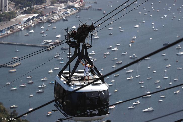 Egy brazil munkás, Diego Scofano, az olimpiai láng stafétájának tagja kezében a fáklyával a Cukorsüveg-hegy tetejére tartó drótkötélpálya egyik kabinjának tetején Rio de Janeiróban 2016. augusztus 5-én, az olimpiai játékok megnyitójának napján.