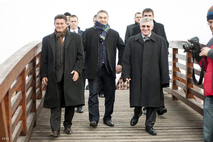 Orbán Viktor miniszterelnök Tasó László országgyűlési képviselő (balra) és Hovánszki György polgármester társaságában érkezik a nyírlugosi labdarúgópálya avatására 2012-ben