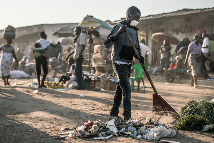 Szemetet seper az utcán egy angolai fiú az egyik járvány-sújtotta területen. Az utcára dobott hulladék ideális költőhely például a sárgalázat terjesztő szúnyogok számára.