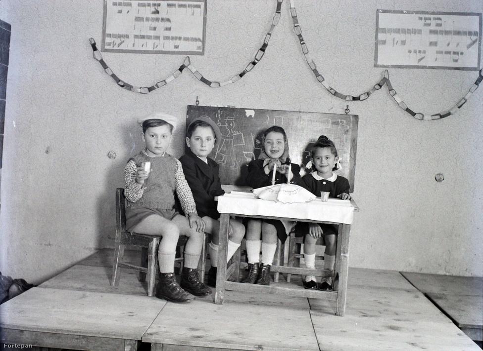 """Óvodások szerepjátéka: apa, anya és a gyerekek várják a szombat bejövetelét. A kendő alatt két kerek fonott kalács, pohárban bor, így szentelték meg a péntek estét. Az ortodox zsidó életre való felkészítés bizonyára a háború előtti óvódai nevelésben is fontos szerepet kapott. Most viszont más feladatokkal is szembe kellett néznie a pedagógusoknak és a gyermekvédőknek. A gyerekek többségének egyik vagy akár mindkét szülője meghalt, ők maguk testileg és lelkileg traumatizálva indultak az életnek. Sok """"apátlan-anyátlan magyar zsidó gyermeket"""" a koncentrációs táborokból már egyenesen Palesztinába vittek (Népszava, 1946. április 11.)."""