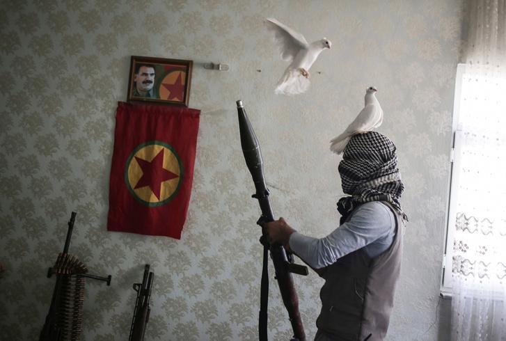 A Kurd Munkáspárt ifjúsági tagozatának egyik tagja pózol fegyverekkel az otthonában.