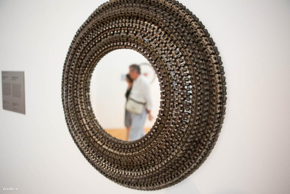 Szintén egy Lolo Palazzo-mű, szintén újrahasznosított bicikliláncból. A falitükör neve Mirror Me, az indusztriális irányzat tökéletes mintadarabja lehetne, akárcsak a tárlat ezen részének további munkái, például Gungl Tibor hulladékfémekből hegesztett asztali lámpája vagy Gulyás Ferenc bárszéke.