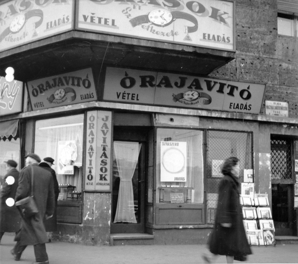 Magyar Jakobinusok tere - Alkotás utca sarok. Ami igazán izgalmas, hogy mennyire vegyes ezeknek az ötvenes évekbeli szolgáltatásoknak a jellege. Az itt látható rövid utcaszakaszon ott van már a Csemege állami presztízsüzlete minőséginek számító élelmiszerekkel, vagy a Vas és Edény, de a szomszédban még hagyományosabb kisipari, kiskereskedelmi egységek lavíroznak.