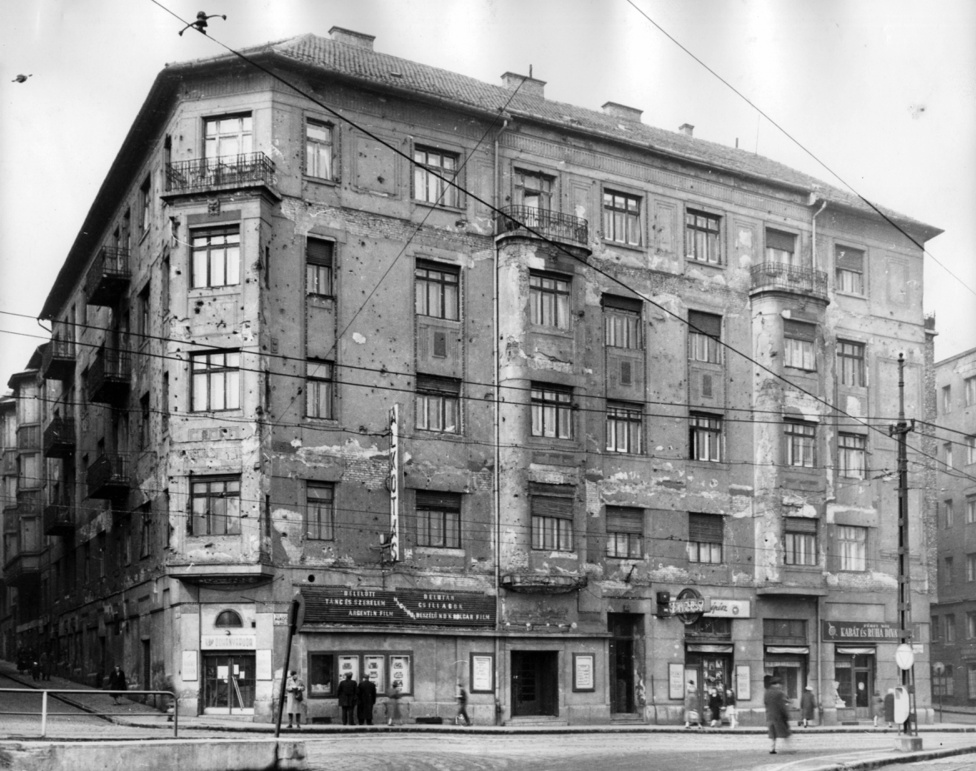 """Alkotás utca 11. Alkotás mozi. Balra a Greguss utca, jobbra a Ráth György utca.Kovács György férfi szabó, és Csapilla József műköszörűs - olvasható a cégéreken. Utóbbiról """"köszörű költőként"""" Tersánszky is megemlékezett: """"A csapszék második szomszédja Csapilla József műköszörűs lakása és akkor még műhelye is volt. Csapillának egészen kitűnő versei jelentek meg a Pesti Hírlapban és más sajtószervekben is. Boldogult feleségem """"Köszörűs költőnek"""" keresztelte el őt"""" - írta az ideje jelentős részét szintén a környék kocsmáiban eltöltő, legszívesebben ott harmonikázgató író."""