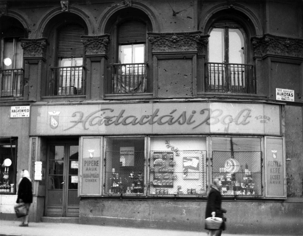 """Nagyenyed utca - Alkotás utca sarok közelebbről.Hasonló maszek szféra Jugoszláviában és Lengyelországban maradt meg még főleg a szocialista blokkban. Ők értelemszerűen  minőségi alternatívát jelentettek a piszkos állami boltokkal és udvariatlan eladókkal szemben. """"A közgondolkozásban a maszek cipész, szabó, kereskedő megbízhatóbbnak tűnt, s voltak olyan tevékenységi körök, ahol a szigorú szabályozás ellenére a magánszektor részesedése a forgalomból magasabb volt, mint az állami vagy szövetkezeti kereskedelemé"""" - írja Valuch Tibor társadalomtörténész."""