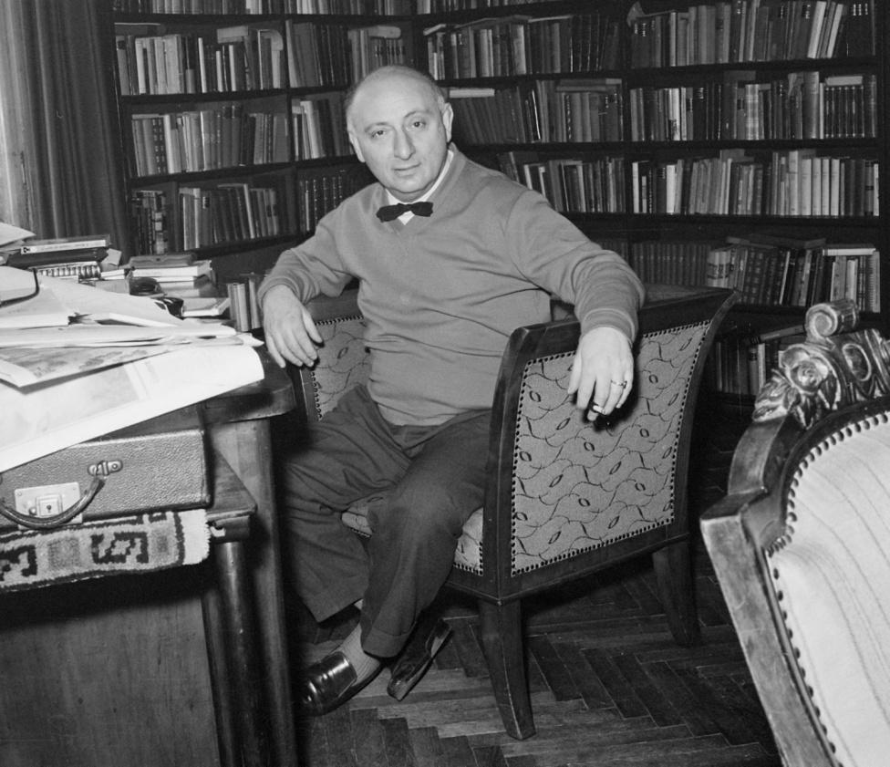 """Vas István (1910-1991) gazdag zsidó polgárfiúként az irodalmat választotta és Kassák Lajos nevelt lányát, a mozdulatművész Nagy Etit, aki pár év házasság után meghalt. A háború alatt munkaszolgálatos volt, 1945-ben Ottlik Géza lakásán bujkált. 1945-ben belépett a Magyar Kommunista Pártba, de 1953-ban kérte párttagság alóli felmentését.                          A hatvanas években sokan szemére vetették, hogy jóban volt Aczél elvtárssal, akinek egyszer 1944-ben lehetőséget adott arra, hogy megmentse az életét. """"Aránylag nagyszerű"""" – mondta állítólag a rendszerről.                          A képen épp a jellegzetes """"vasnyakkendő"""" (vagyis egy nem vagy félig megkötött kravátli) helyett polgári csokornyakkendőben ül íróasztala mellett."""