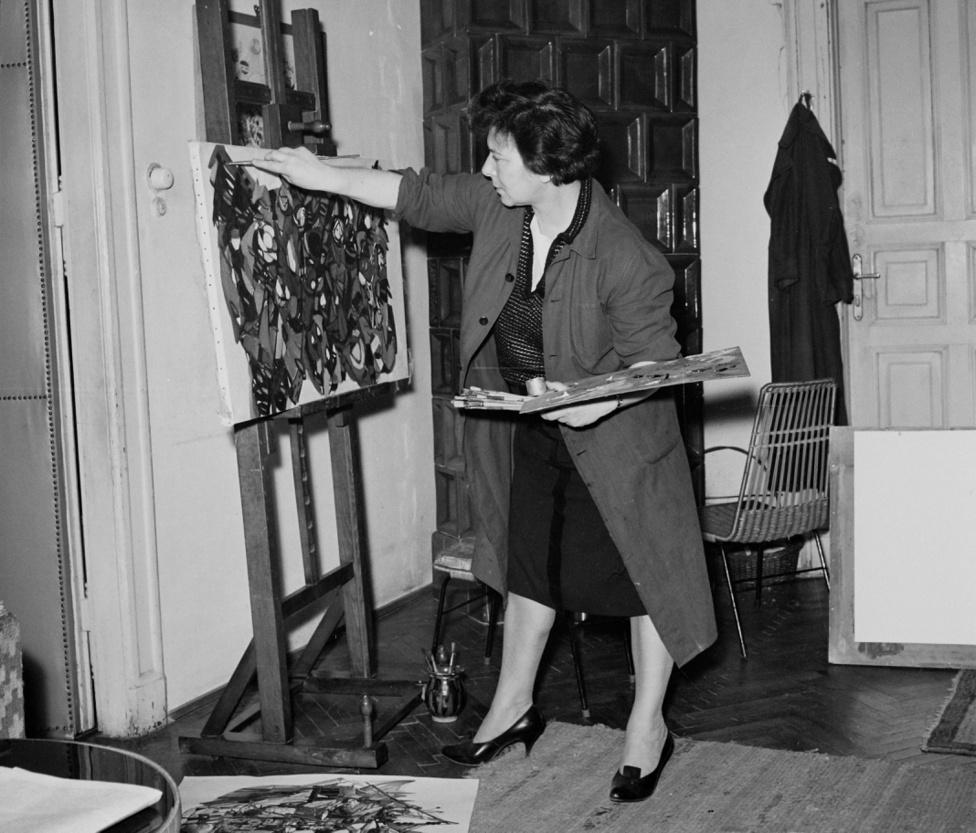 Szántó Piroska (1913-1998) a Várkert rakpart 17. első emeleti lakásban. A festőnő Szőnyi István tanítványa volt a Képzőművészeti Főiskolán, majd csatlakozott a Szocialista Képzőművészek Társaságához, aztán a Szentendrén együtt dolgozott Bálint Endrével, Korniss Dezsővel, Vajda Lajossal. Itt ismerkedett meg Vas Istvánnal is, akivel évekig folyt szenvedélyes, se vele-se nélküle kapcsolata.                         Ami az ötvenes években az elhallgattatott íróknak és költőknek a műfordítás volt, az volt a művészeknek a könyvillusztráció: Szántó Piroska Villont, Shakespeare-t, Krúdyt illusztrált. A hatvanas években már Párizsban és Rómában is kiállíthatott.
