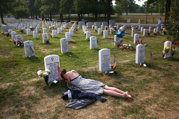 Elhyunt barátját gyászolja egy nő az Arlington Nemzeti Sírkertben, ahová Irakban és Afganisztánban elhunyt katonákat temettek.