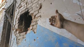 Kedves arc mosolyog egy szétlőtt ház faláról