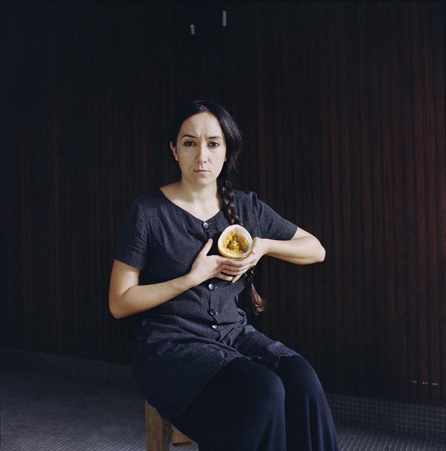 """""""Fiatal nők és gyümölcsök közös portréit készítem el, minthogy São Paulo – ott születvén – számomra a termékenység és a fogantatás jelképe, mind fizikai és szakrális értelemben. A műtermem utcai terek, többnyire kék sarkok és falak szolgálnak háttérül. """" - írta pályázatában Ember Sári."""