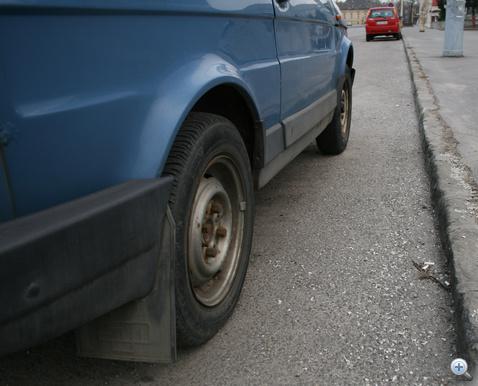 Kis jóindulattal kevesebb, mint harminc centiméter van az autó és a padka között. Vicces, de nem tudott közelebb állni: amikor leparkoltak vele, még embermagasságú hótorlaszok voltak errefelé.