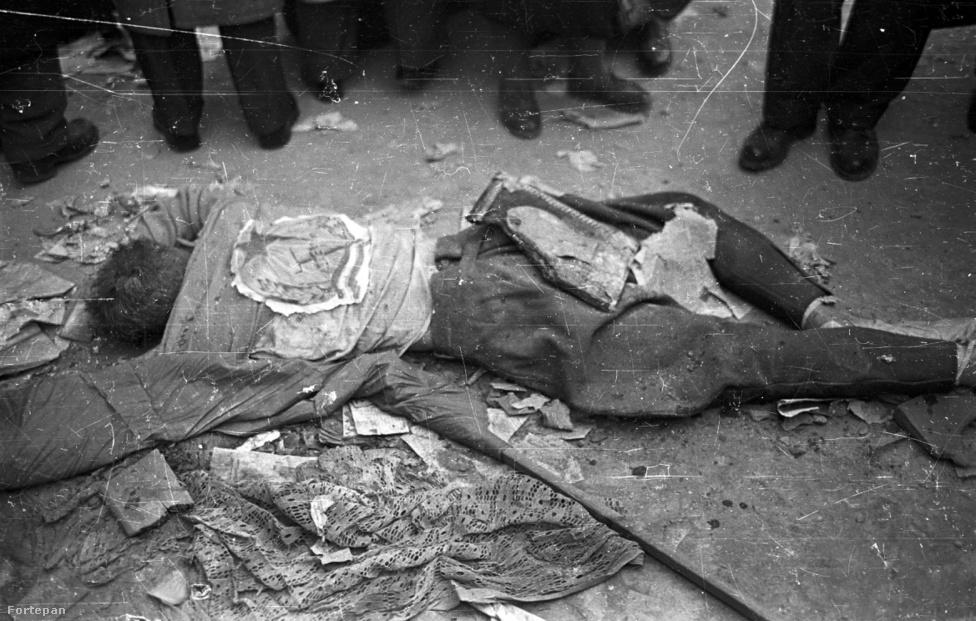 Ugyanott és ugyanakkor, a pártház ostromakor kivégzett egyik védő maradványai Rákosi címerrel, mellette összegyűrt vörös zászló.