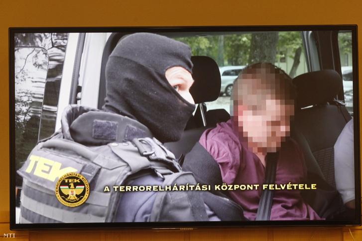 A férfi elfogásakor készült felvételt mutatják be egy tv-n a rendőrség sajtótájékoztatóján.