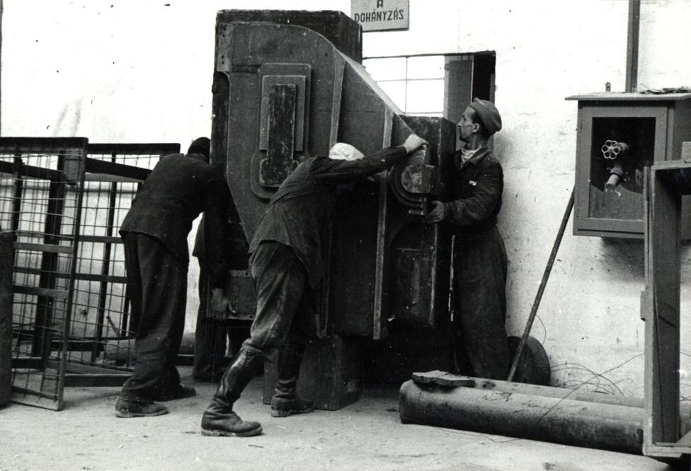 """""""Gyár. Épületjavítóüzem. A mintaasztalos műhely ajtaja oly kicsi, hogy a nagy mintákat elkészítésük után ujból szét kell szedni, hogy az ajtón kiszállíthassák."""""""