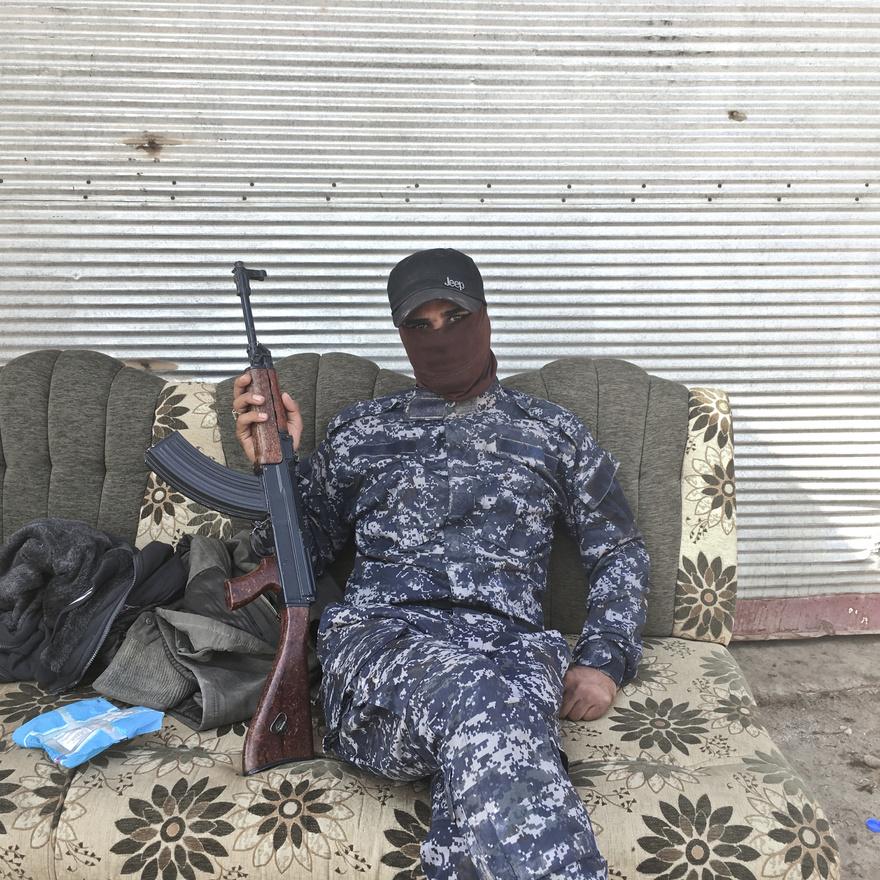 Abduljuszef az Iraki Állami Rendőrség egyenruhájában pózol egy Moszul melletti faluban, 40 kilométerre a harcoktól.
