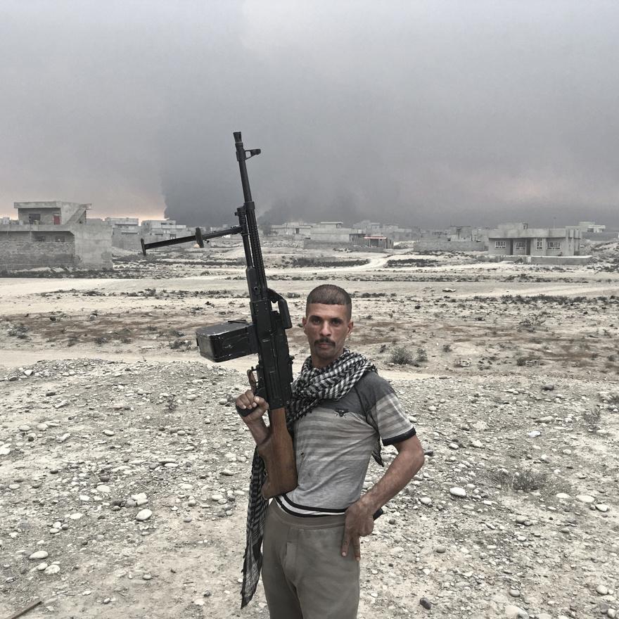 Haidar Husszein az iraki hadsereg katonája, de láthatóan nem egyenruhában harcol, pedig ez a kép ugyanott készült róla, ahol a sorozat többi arcáról. Mögötte a háttérben a harcok füstje is látszik.