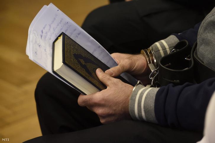 Koránt és jegyzeteket tart megbilincselt kezében a röszkei közúti átkelőnél 2015. szeptember 16-án történt tömegzavargás miatt terrorcselekmény elkövetésével vádolt Cipruson élő szír férfi az ellene folytatott büntetőper tárgyalásán a Szegedi Törvényszéken 2016. november 30-án.