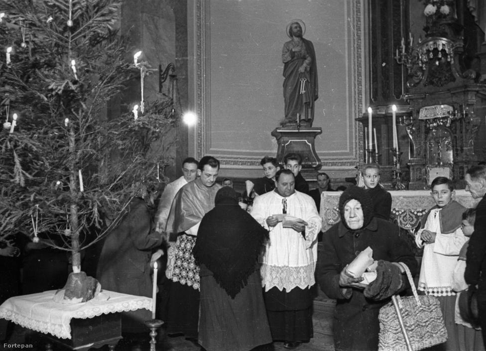"""Karácsonyi adományosztás az ötvenes évek végén. Biztosan a néni is örült, de azért a legszebb karácsonyi ajándékot mégis Rákosi Mátyás adta 1953 karácsonyán a katolikus egyháznak. """"Mozgalmunk [a békepapság] kérésére Népköztársaságunk kormánya karácsonyra 35 megtévedt testvérünknek adott amnesztiát. Már az is megható gesztus volt, hogy éppen szentestére lettek szabadok. Ezek a testvérek tudják, hogy kinek köszönhetik szabadulásukat. Nem szabad őket magukra hagynunk és nem szabad őket átengednünk a reakciós gengszterkedésnek. Törődnünk kell velük"""" – adott hírt egy szép karácsonyról A Kereszt."""