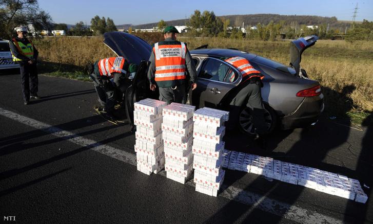 A (NAV) munkatársai egy előzőleg az árokba borult cseh rendszámú autóban talált csempészett dohányárut pakolják ki az M1-es autópályán 2015-ben