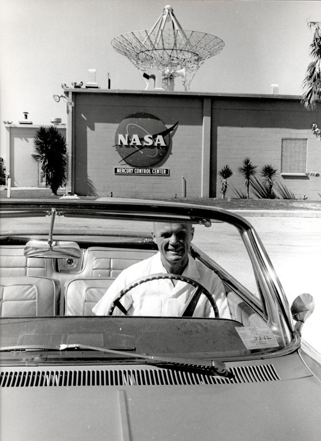 Floridai napfényben: Glenn autójában, a háttérben a Mercury vezérlőközpont.