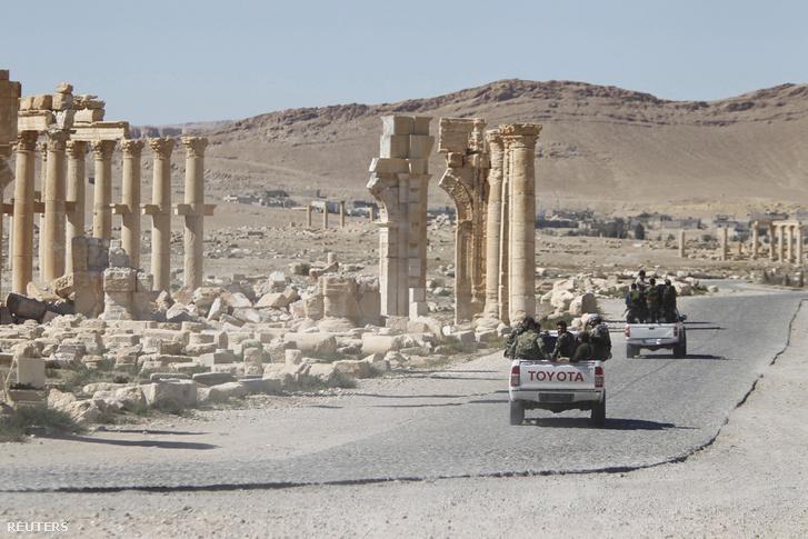 A szír kormány katonái haladnak el Palmüra romvára mellett 2016. április 1-én